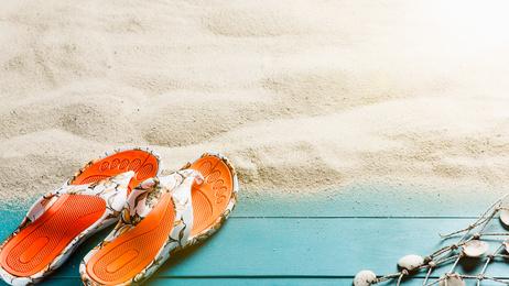 Holzplanken und Sandstrand mit Urlaubsutensilien