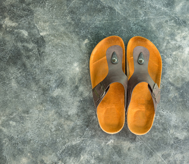 pair of brown leather sandal on concrete texture background, copy space