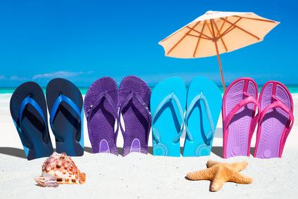 Bunte Flip Flops in einer Reihe mit Muscheln und Sonnenschirm